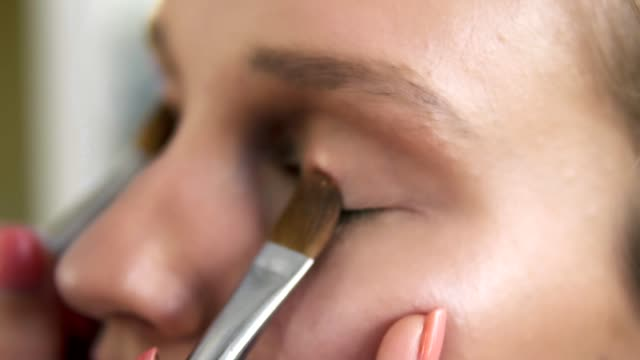 The-make-up-artist-puts-light-shiny-eyeshadow-on-a-model-s-eyelids-using-two-professional-brushes-Close-up-Make-up-process