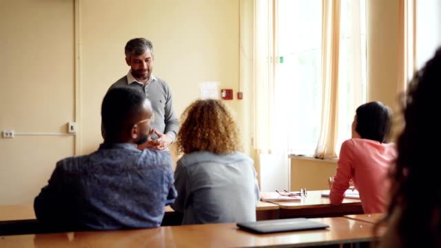Curioso-estudiante-es-levantar-la-mano-y-preguntan-su-maestro-experimentado-está-contestando-le-con-sonrisa-Profesión-educación-y-aprendizaje-concepto-