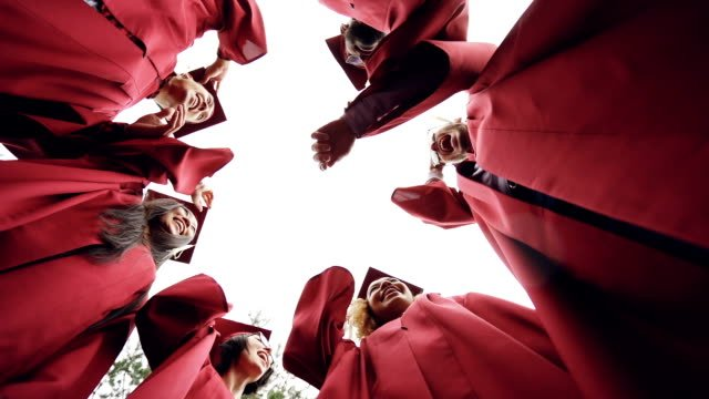 Slow-motion-low-angle-shot-of-graduates-standing-in-circle-throwing-mortar-boards-in-the-sky-and-laughing-Togetherness-friendship-and-modern-lifestyle-concept-