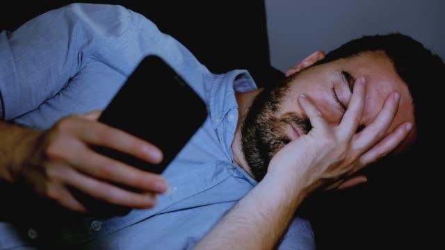 Un-hombre-triste-leyendo-malas-noticias-en-el-teléfono-móvil