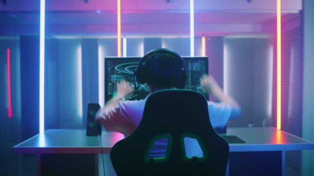 Professional-Gamer-Playing-and-Winning-in-First-Person-Shooter-Online-Video-Game-on-His-Personal-Computer-Footage-Fade-out-into-Bokeh-Room-Lit-by-Neon-Lights-in-Retro-Arcade-Style-Cyber-Sport-Championship-