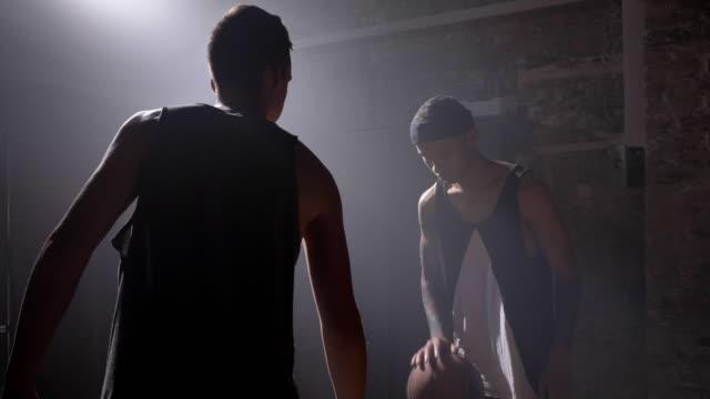 Jugador-de-baloncesto-bloqueando-la-bola-de-otro-jugador-durante-el-juego-jugando-en-el-interior-en-sala-con-proyector