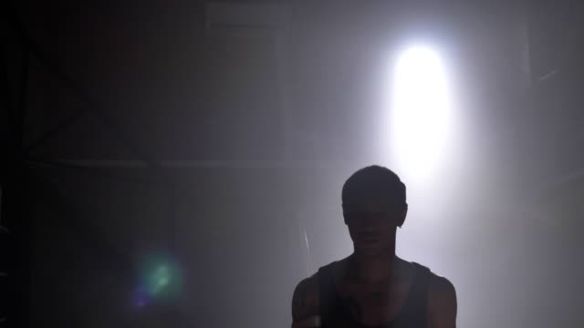One-basketball-player-silhouette-playing-with-ball-in-dark-misty-room-with-floodlight