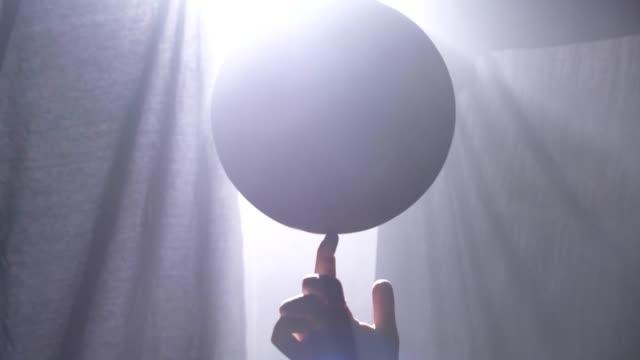 Bola-de-giro-de-jugador-de-baloncesto-en-un-dedo-en-cuarto-oscuro-brumoso