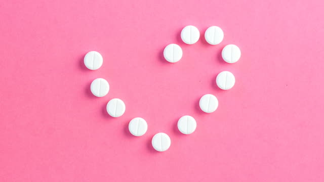 Heart-shaped-of-white-pills-on-pink-background