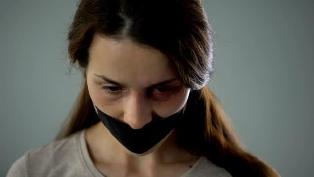 Geknickte-Frau-mit-getapten-Mund-leider-Blick-in-Kamera-Opfer-von-Missbrauch