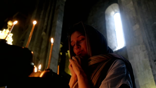 Mujer-en-velo-rezando-ante-un-icono-en-la-iglesia-católica-ortodoxa