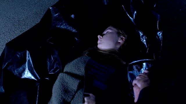 Muerto-joven-en-bolsa-de-plástico-en-la-escena-del-crimen-examinando-el-cadáver-del-agente-de-la-policía