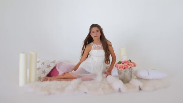 girl-sits-and-poses-near-pillows-candles-and-flowers