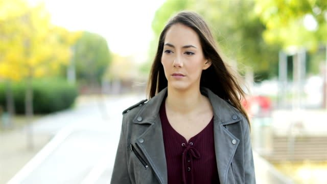 Serious-pensive-woman-walking-in-a-park