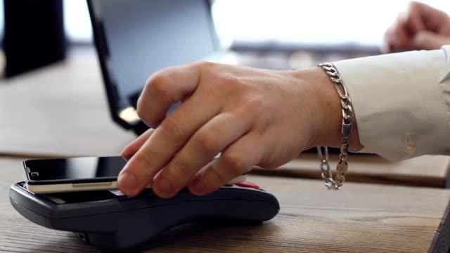 El-empresario-paga-un-acuerdo-con-el-sistema-nfc-sin-contacto-en-la-oficina-con-un-smartphone