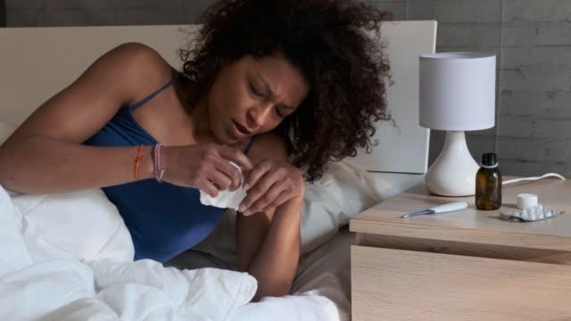Una-mujer-negra-soplar-la-nariz-en-la-cama