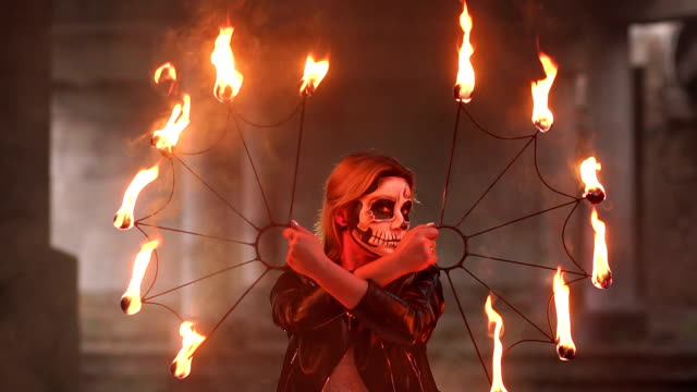 Creepy-bride-with-makeup-on-her-face-holding-burning-torches-Halloween-