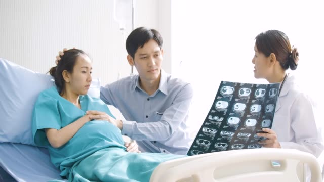 Doctor-showing-X-ray-scan-results-to-pregnant-woman-and-her-husband-with-serious-emotion-People-with-healthcare-and-medical-concept-