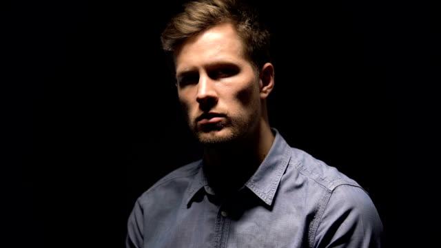 Flashing-lights-illuminating-young-man-on-dark-background-suspected-crime