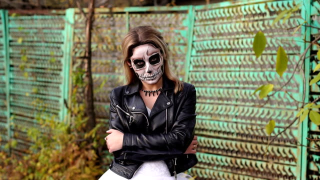 Creepy-bride-with-makeup-in-the-form-of-skull-on-the-background-of-an-old-fence-