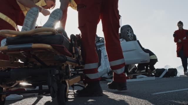 Verkehrsunfall-mit-Autounfall:-Feuerwehr-führt-Mutter-zu-einem-Kind-das-auf-Stretchern-liegt-die-Sanitäter-retten-/-reanimieren-Überrollfahrzeug-mit-anderen-eingeklemmten-Passagieren-im-Hintergrund