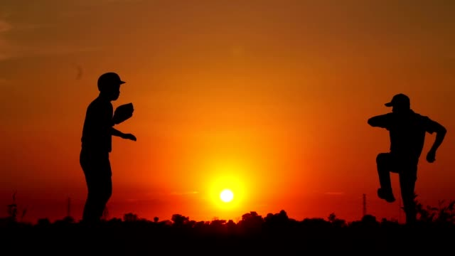 Silhouette-baseball-two-men-were-practicing-throwing-a-baseball-and-getting-together