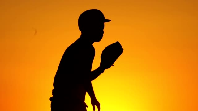 Silhouette-man-with-a-baseball-glove-catching-a-baseball