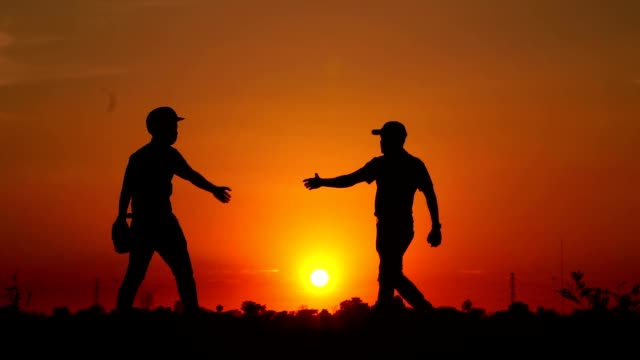 Silhouette-baseball-two-men-coordinated-with-a-handshake
