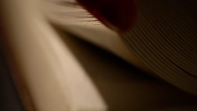 Hojeando-un-viejo-páginas-del-libro-de-la-mano