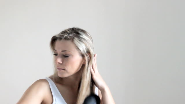 Beautiful-blonde-woman-with-long-hair-angry-about-loosing-it-after-brushing
