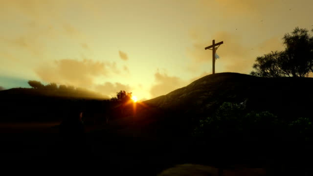 Woman-praying-at-Jesus-cross-against-beautiful-sunrise-panning