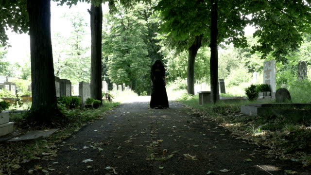 Woman-in-mourning-black-clothes-walking-slowly-on-alley-in-cemetery-holding-a-flower-crown-in-her-hand-portrait-of-sorrow-and-loneliness