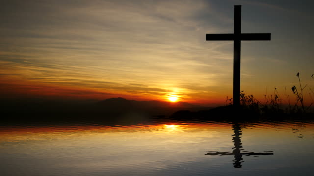 Cross-of-Jesus-Christ-near-Water-with-Sunset-and-Peaceful-Mood-