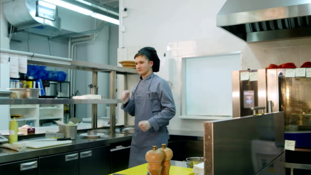 Funny-young-male-cook-dancing-in-the-professional-kitchen