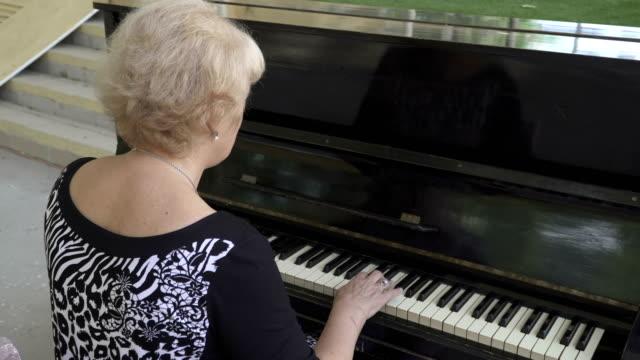 Porträt-einer-alten-Frau-die-Klavier-spielen