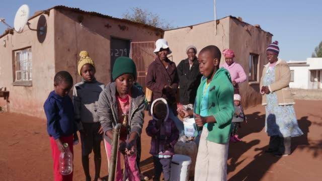 Niños-africanos-el-agua-potable-de-un-grifo-mientras-mujer-fila-para-recoger-el-agua-en-envases-de-plástico-debido-a-la-sequía-en-África-del-sur