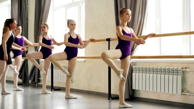 Niñas-serias-están-aprendiendo-la-secuencia-de-posiciones-de-ballet-en-clase-de-ballet-con-el-maestro-ayuda-Luz-amplias-baile-salón-con-grandes-ventanas-y-barra-de-ballet-es-visible-