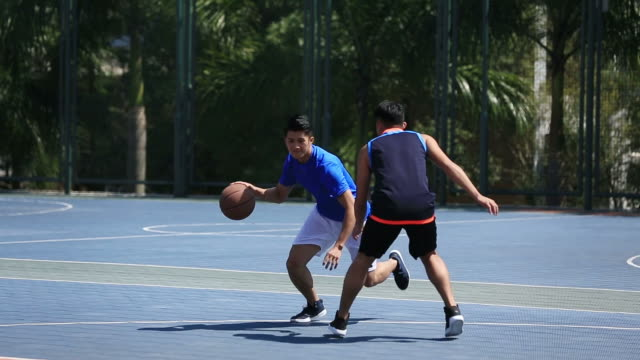 young-asian-basketball-player-playing-on-outdoor-court