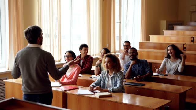 Fröhliche-Schüler-heben-Hände-um-Lehrer-Fragen-zu-beantworten-Professor-bärtigen-Mann-ist-auf-junge-Menschen-zeigen-und-ihnen-zuzuhören-Unterricht-und-Hochschulen-Konzept-