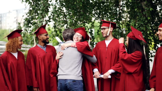 Lenta-de-profesor-universitario-abrazando-a-sus-estudiantes-y-agitando-las-manos-en-el-día-de-la-graduación-con-alegría-y-orgullo-Árboles-verdes-edificio-de-la-institución-educativa-es-visible-
