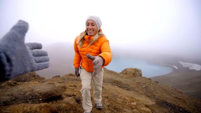 Joven-senderismo-saca-la-mano-para-llegar-a-uno-de-su-compañero-de-equipo-Una-mano-para-llegar-a-la-cima-de-la-montaña-Excursionista-ayuda-a-su-compañero-de-equipo-para-llegar-a-la-cima-de-la-montaña-sobre-el-lago-de-cráter-volcánico-en-Islandia