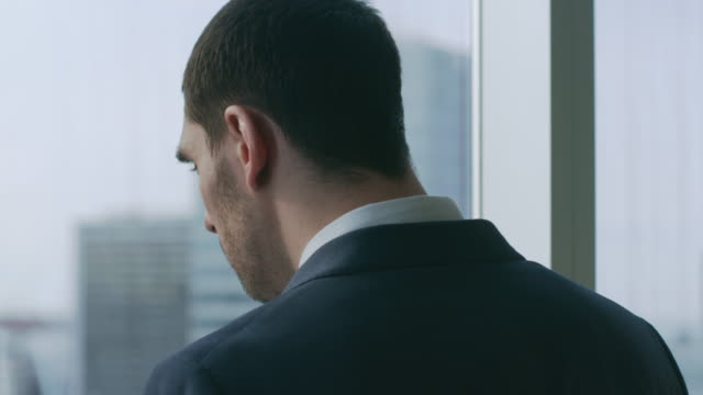 Close-up-Shot-of-the-Confident-Businessman-in-a-Suit-Standing-in-His-Office-and-Making-Phone-Call-so-He-can-Close-the-Deal-Looking-out-of-the-Window-Big-City-Business-District-Panoramic-View-