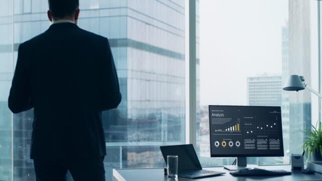 Empresario-confío-en-un-juego-de-pie-en-su-oficina-mirando-fuera-de-la-ventana-y-hacer-llamada-de-teléfono-importante-para-que-puedan-cerrar-el-trato-Escritorio-con-ordenador-Personal-en-él-muestra-análisis-gráficos-y-estadísticas-Vista-panorámic
