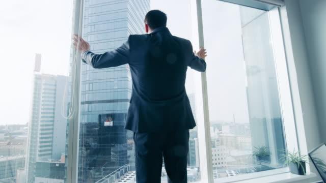 Tras-el-golpe-del-hombre-de-negocios-confía-en-un-traje-de-caminar-a-través-de-su-oficina-y-mirando-por-la-ventana-cuidadosamente-Negocios-moderno-con-estilo-oficina-con-ordenador-y-vistas-a-la-gran-ciudad-