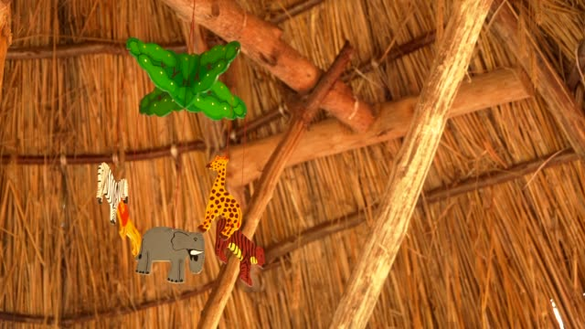 Rattle-above-the-crib-is-spinning-animals-hang-on-it-against-the-ceiling-of-wood-and-reeds-There-s-no-one-the-toy-is-spinning