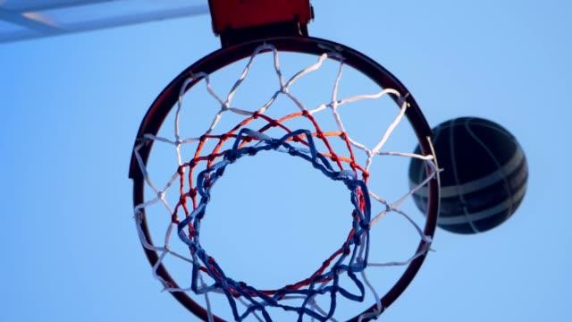 Baloncesto-choca-con-aro-y-pasando-por-anillo-gimnasio-al-aire-libre-con-azul-cielo