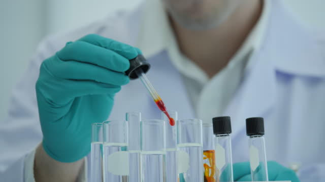 Close-up-of-a-scientist-with-a-pipette-analyzes-a-colored-liquid-to-extract-the-DNA-and-molecules-in-the-test-tubes