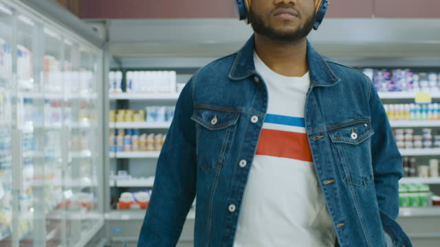 At-the-Supermarket:-Stylish-African-American-Guy-with-Headphones-Walks-Through-Frozen-Goods-Section-of-the-Store-Following-Back-View-Shot-Slow-Motion-