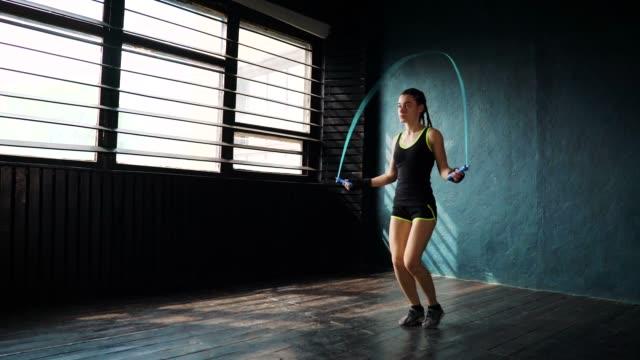 Joven-boxeador-mujer-serio-útil-en-vendaje-envuelto-puño-manos-saltando-sobre-saltar-la-cuerda-en-el-gimnasio