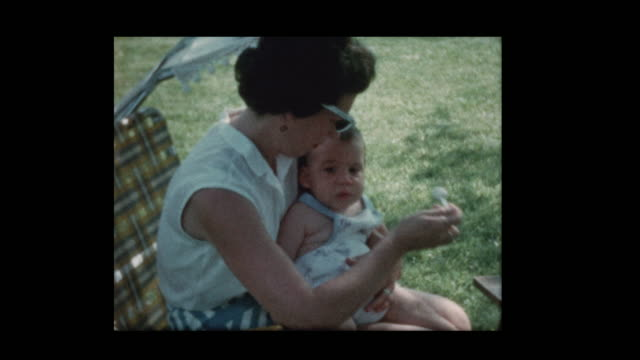 1960-Mom-feeds-baby-sitting-outside-on-lawn-chair