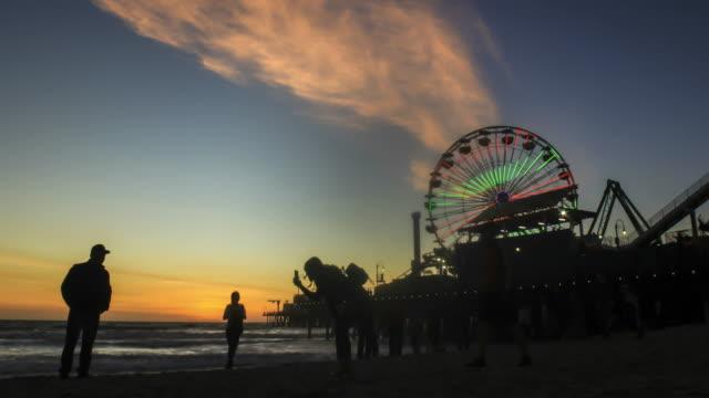 People-enjoying-sunset-next-to-the-Santa-Monica-Pier---day-to-night-4k-time-lapse