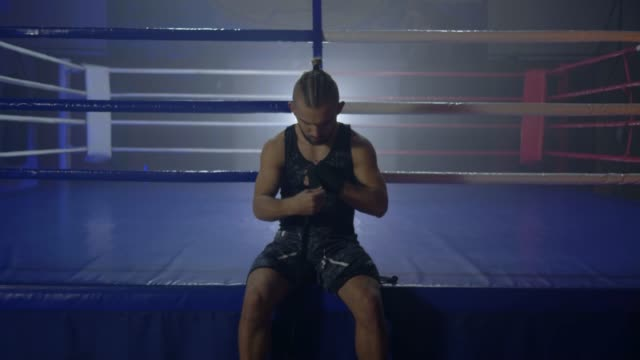 attractive-boxer-reel-up-black-bandages-for-Kickboxing-before-fight-sitting-near-ring