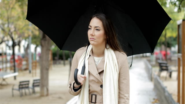 Frustrated-woman-walking-complaining-under-the-rain