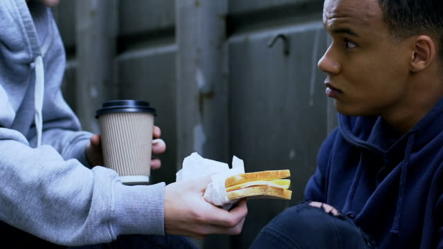 Kind-boy-sharing-tasty-sandwich-and-warm-coffee-with-gamin-human-compassion
